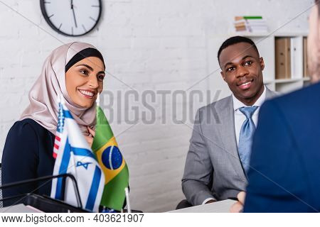 Smiling African American And Arabian Business Partners Looking At Interpreter On Blurred Foreground