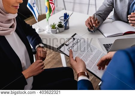 Cropped View Of Interpreter Holding Contract During Meeting With Multicultural Business Partners, Bl