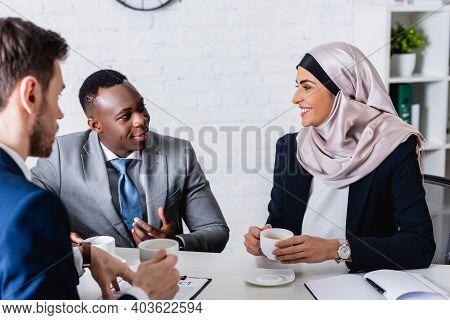Smiling African American Businessman Gesturing Near African American Businessman And Interpreter Hol