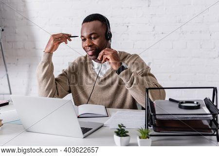 Smiling African American Interpreter In Headset Holding Pen While Working At Laptop In Translation A