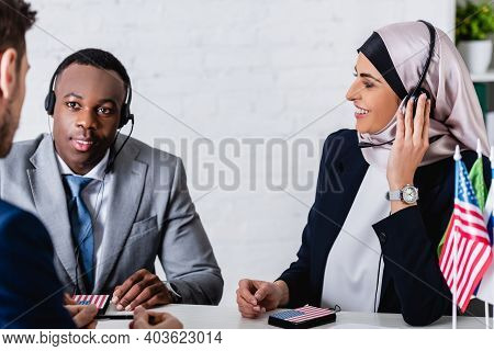 Smiling Arabian And African American Business Partners In Headsets Near Interpreter On Blurred Foreg