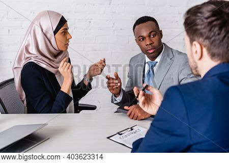 Multicultural Businesspeople Gesturing While Discussing Contract Near Interpreter, Blurred Foregroun