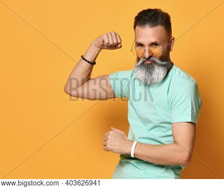 Grey-haired Brutal Bearded Man In Casual Trendy Outfit Showing Muscle, Power Or Strong Gesture Demon