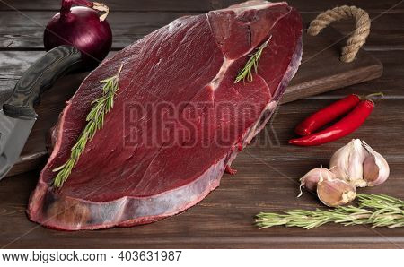 Piece Of Fresh Raw Meat On A Wooden Background. Meat And . Moose Meat Is Considered One Of The Most