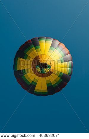 Down View Of A Hot Air Balloon In The Sky. Basket Lifting Flying Up In A Blue Sky. View From Down Be