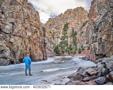 senior male hiker in a canyon of mountain river in winter scanery - Poudre RIver at Little Narrow above Fort Collins, Colorado