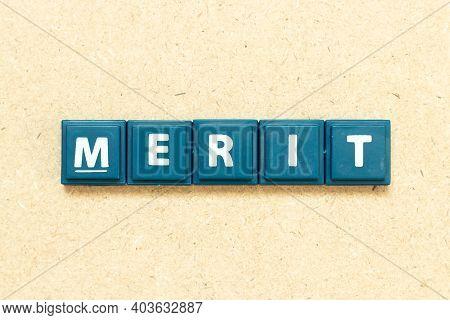 Tile Alphabet Letter In Word Merit On Wood Background