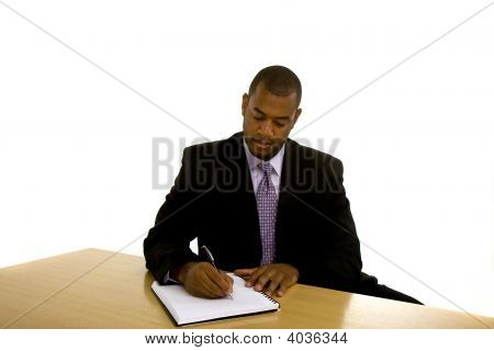 Black Man Writing At Desk Looking Down