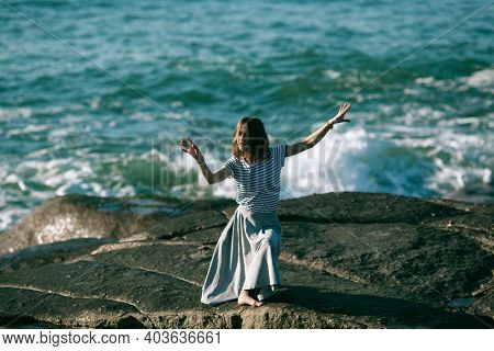 The young dancers woman is engaged in choreography on the rocky coast of the ocean.