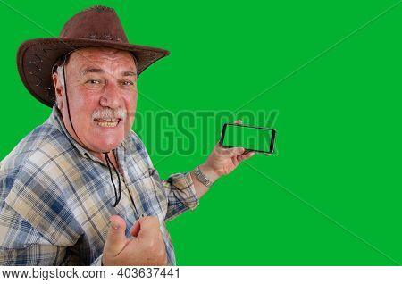 An Elderly Rancher Joyfully Recommends Something While Looking At The Camera. He Is Holding A Smartp