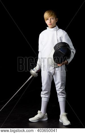 Boy In A Fencing Suit Holding A Mask And Saber. Portrait Of A Confident Teenager Wearing A White Swo
