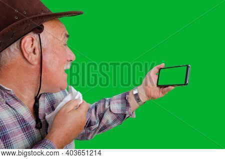 An Elderly Rancher In A Plaid Shirt Is Arguing With Someone On His Mobile Phone Excitedly. He Is Hol