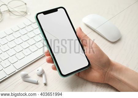 Mykolaiv, Ukraine - July 8, 2020: Woman Holding Iphone 11 Pro Max With Blank Screen At Workplace, Cl