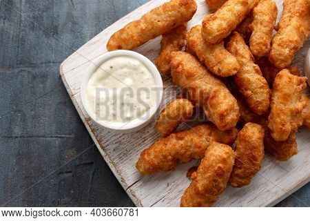 Battered Haddock Fish, Mini Fingers With Mashed Peas, Tartar Sauce On White Wooden Board