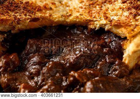 British Beef Steak Pie With Onion, Wine Gravy On Rustic Stone Board