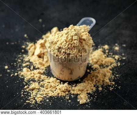 Scoop Of Pea Vegan Protein Powder On Dark Rustic Background. Sport Nutrition.