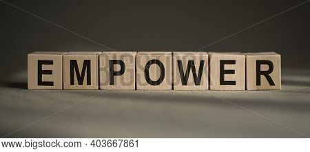 A Wooden Blocks With The Word Empower Written On It On A Gray Background.