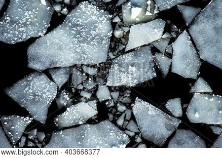 Ice Drift On The River In Spring, Top View - Ice Floes On A Black Background