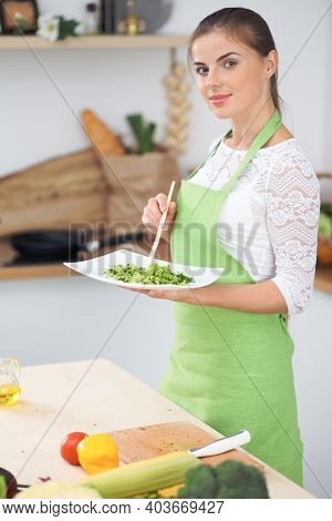Young Woman Housewife Cooking In The Kitchen. Concept Of Fresh And Healthy Meal At Home