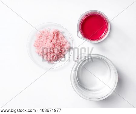 Close Up Inorganic Chemical On White Laboratory Table (top View). Pink Flake Chemicals In Chemical W