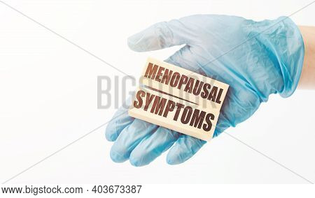 Doctor's Hand In Blue Glove Shows The Wooden Cubes With Text Menopausal Symptoms Medical Concept.