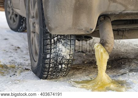 Frozen Yellow Water Condensate With Gasoline From The Exhaust Pipe Of A Car On The Snow In The Cold
