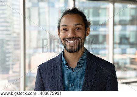Headshot Portrait Of Smiling Ethnic Businessman In Office