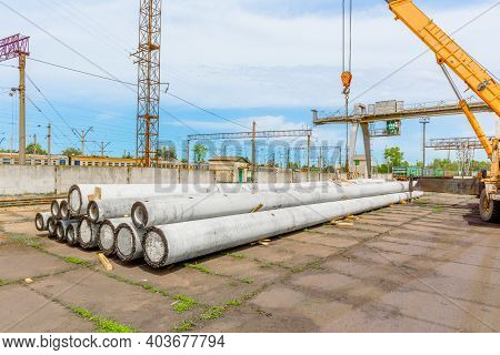 Unloading Of Concrete High-voltage Poles At The Construction Site Using A Lifting Crane