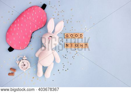 Healthy Sleep Concept. Amigurumi Hare With Alarm Clock And Sleep Mask On A Blue Background With Conf