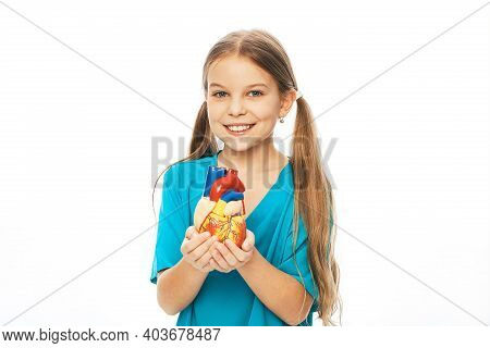 Girl Holding An Anatomical Heart Model In Hands. Concept Of Cardiac Health And Diagnosis Of Children