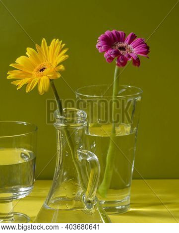 Gerberas In Glass Bottles On A Green Background. A Floral Minimalistic Concept In A Modern Interior