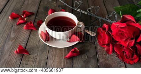 Cup Of Tea With Red Roses And Hearts On Dark Vintage Planks. Breakfast Background For Valentines Day