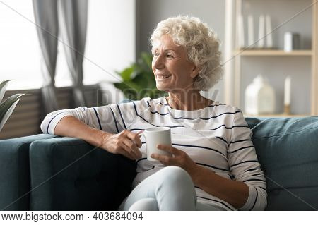Dreamy Middle Aged Mature Caucasian Woman Enjoying Peaceful Morning Time.