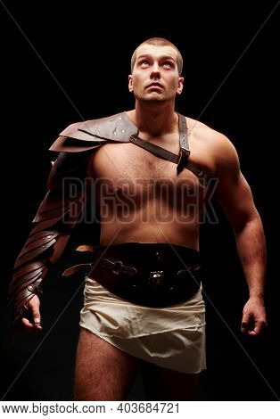 Gladiator With Sword And Armor On A Black Background. A Warrior In Gladiatorial Armor Looks Up At A