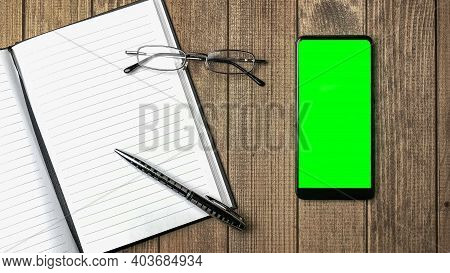 Top View Of Open Notebook With Blank Pages And Cell Phone With Green Screen, Glasses On Wooden Table