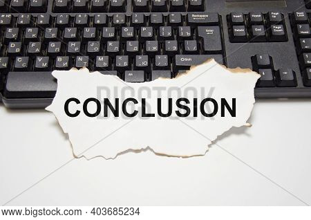 The Word Conclusion Is Written On A White Sheet Of Paper That Lies On The Computer Keyboard