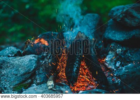 Vivid Smoldered Firewoods Burned In Fire Close-up. Atmospheric Warm Background With Orange Flame Of