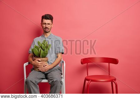 Upset Crying Unshaven Man Feels Lonely Poses Alone Holds Potted Cactus Expresses Negative Emotions I