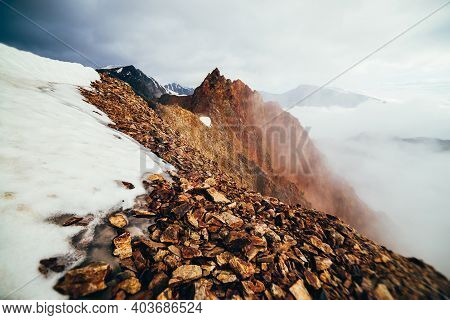 Beautiful Pointy Rocky Pinnacle On Mountain With Snow Among Thick Low Clouds. Atmospheric Minimalist