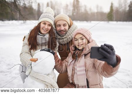 Portrait Of Happy Family Taking Selfie Photo Outdoors While Building Snowman Together And Enjoying W