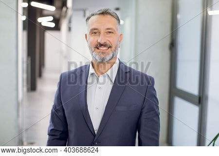 Close Up Front View Of Happy 50-aged Bearded Businessman In Formal Wear, Posing To Camera With Smile