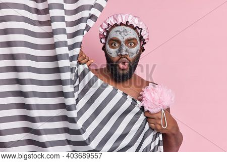Photo Of Shocked Bearded Man Poses In Bathroom Applies Clay Beauty Mask On Face To Refresh Skin And