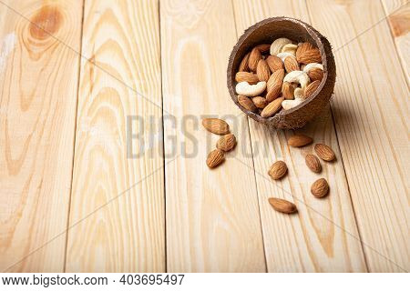Mix Of Almonds, Cashew Nuts In Coconut Bowl On Wood Table Copy Space. Vegan Protein Source