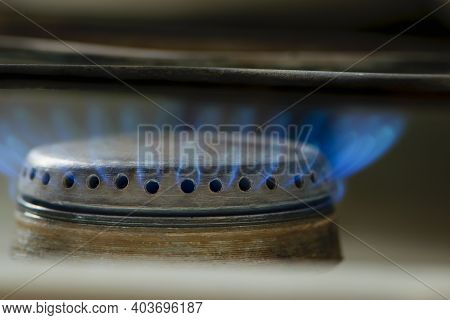 Burning Gas Stove. Blue Flame Close-up. Blue Fire Burns Natural Gas On A Kitchen Stove. Steel Panel