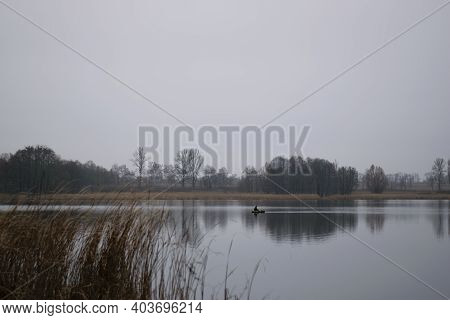 A Fisherman On A Boat On The River. A Quiet Big River And A Boat With A Fisherman. Autumn Background