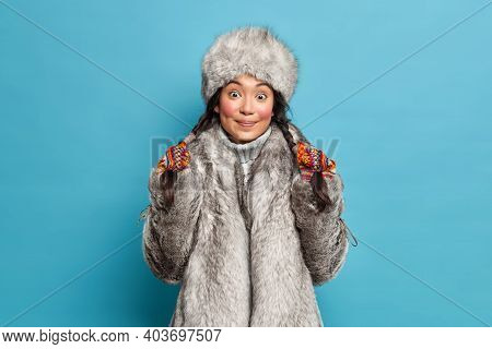 Pretty Surprised Young Asian Woman Holds Pigtails Dressed In Outerwear Isolated Over Blue Background