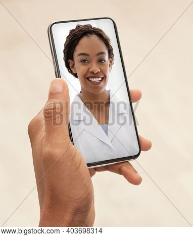 Smiling Black Female Doctor Consulting Patient Via Video Call On Smartphone. Unrecognizable African