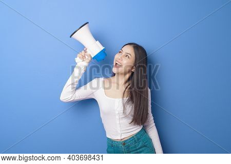 Portrait Of Young Beautiful Smiling Woman Is Using Megaphone To Announce Over Isolated Blue Backgrou