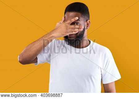 Curious African American Man Peeking Covering Eyes Looking At Camera Through Fingers Posing Standing