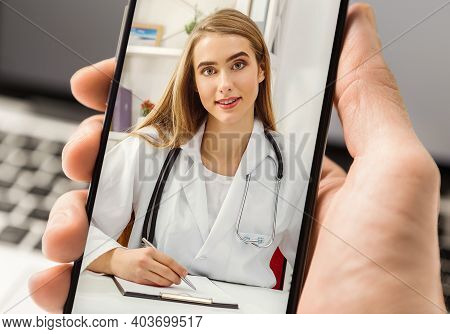 Unrecognizable Man Calling Doctor Online Via Video Call On Smartphone, Having Virtual Medical Consul